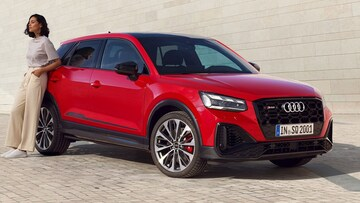 Front-side view of the Audi SQ2 with a woman leaning against the car.